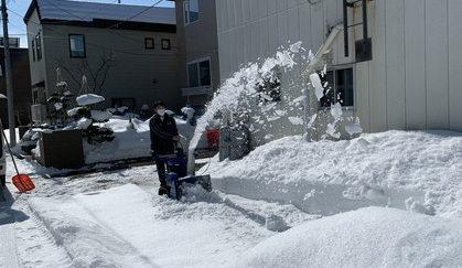 除雪機で作業する便利屋